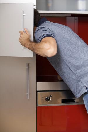 vertical fridge: Young man looking in refrigerator
