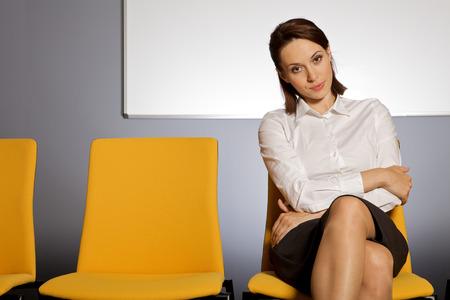 legs crossed on knee: Portrait of businesswoman sitting in waiting room