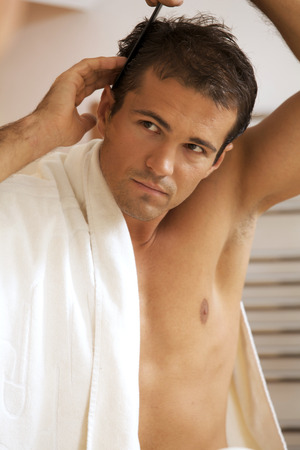 self conceit: Young man combing his hair