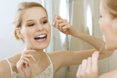 pureness: A young woman flossing her teeth