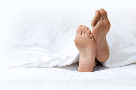 feet crossed: Persons foot in bed LANG_EVOIMAGES
