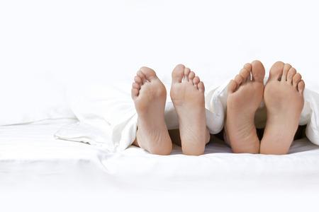 Paar Füße auf dem Bett
