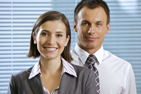 two persons only: Portrait of smiling businessman and woman in office