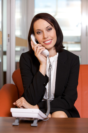 raised eyebrow: Businesswoman conversing on landline phone, portrait