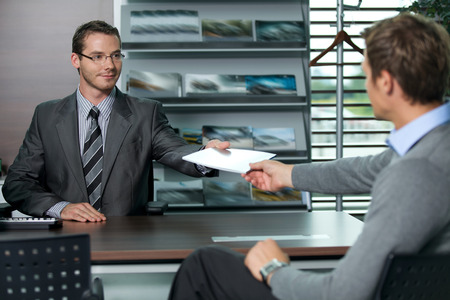 salesperson: Car salesperson giving catalog to businessman LANG_EVOIMAGES