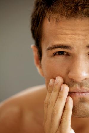 shaving cream: Close-up of young man applying shaving cream