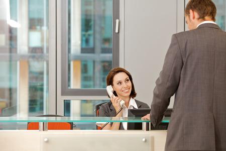 file clerk: Young caucassian secretary assisting businessman LANG_EVOIMAGES