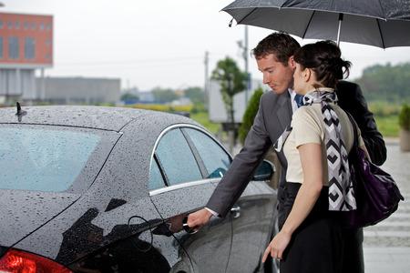 abriendo puerta: Hombre joven que abre la puerta del coche para la mujer