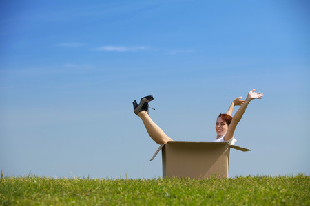 cardboard only: Cheerful young woman sitting in cardboard box at park with arms outstretched LANG_EVOIMAGES