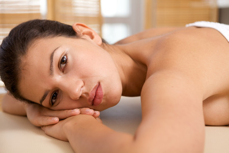 massage  table: Portrait of young woman relaxing on massage table