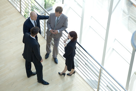 Businessmen and woman standing together by railing conversing Stock Photo