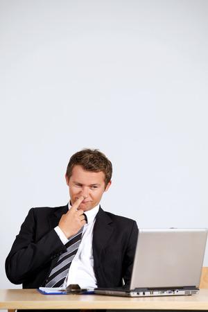 nose picking: Businessman picking nose, looking at laptop in office