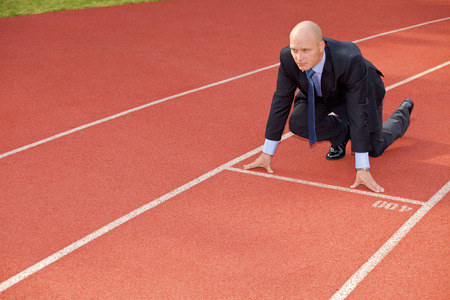 sports track: Businessman at the start line of running track