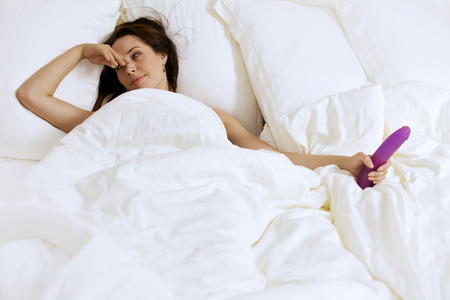 sex toy: Young woman holding dildo on bed