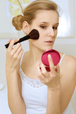 mujer maquillandose: Una mujer de aplicar el maquillaje