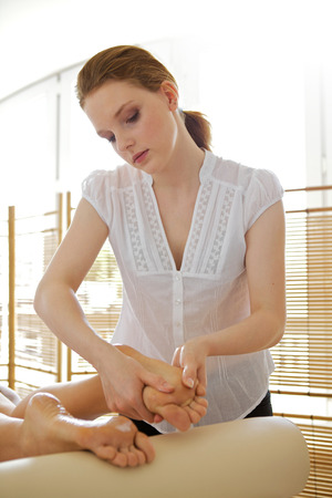 masseuse: Young woman receiving foot massage from masseuse
