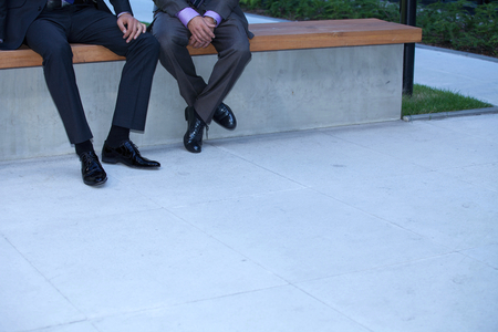 two people only: Businessmen sitting on wall