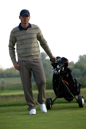 golf bag: Portrait of young man carrying trolley with golf bag