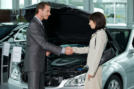 salesperson: Car salesperson shaking hands with customer at showroom