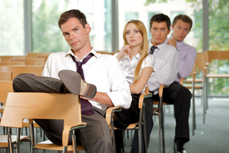 lost in thought: Business executives sitting in row at office LANG_EVOIMAGES