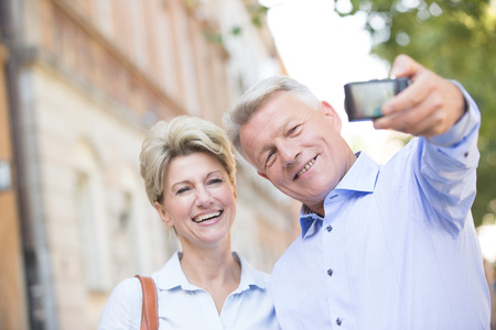 50s adult: Cheerful middle-aged couple taking self portrait outdoors
