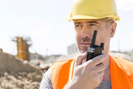 supervisor: Confident supervisor using walkie-talkie at construction site LANG_EVOIMAGES
