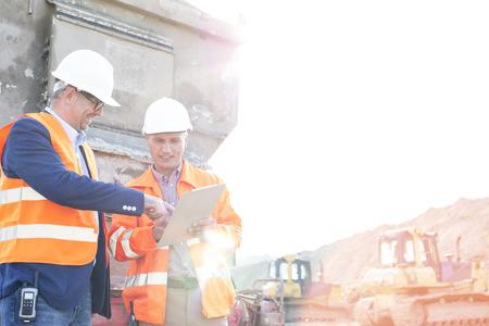 supervisores: Supervisores felices que discuten sobre portapapeles en el sitio de construcción contra el cielo claro