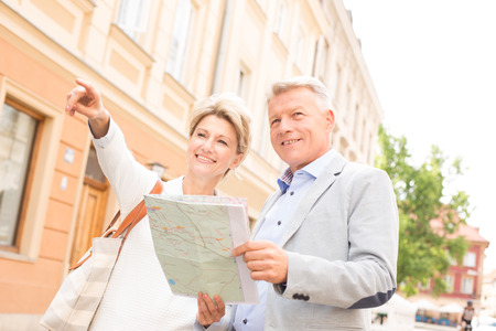 50s adult: Middle-aged woman showing something to man with road map in city