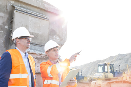 building contractor: Supervisor showing something to colleague at construction site on sunny day LANG_EVOIMAGES
