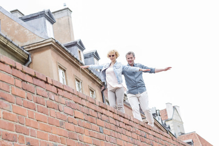���clear sky���: Low angle view of middle-aged couple with arms outstretched walking on brick wall against clear sky