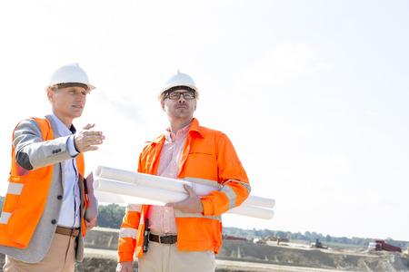 supervisores: Los supervisores con los modelos de discutir en el sitio de construcción contra el cielo claro LANG_EVOIMAGES