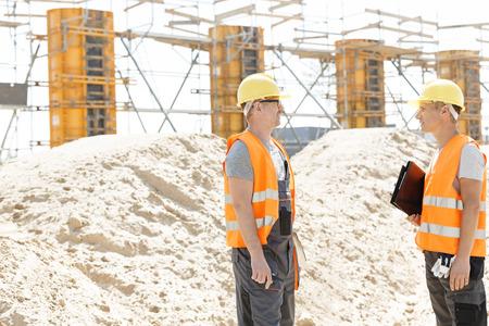 supervisores: Vista lateral de los supervisores que discuten en el emplazamiento de la obra