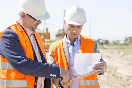 supervisores: Los ingenieros que examinan documentos en el portapapeles en el sitio de construcción contra el cielo claro