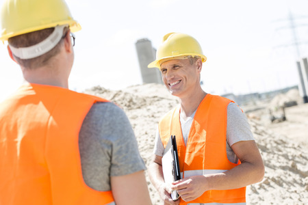 supervisor: Happy supervisor discussing with colleague at construction site LANG_EVOIMAGES