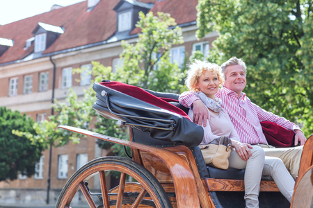 horse cart: Happy middle-aged couple sitting in horse cart on city street LANG_EVOIMAGES