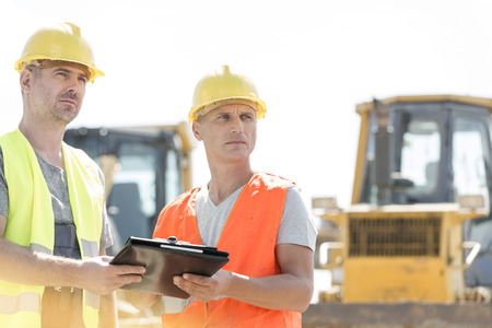clear away: Engineers looking away while holding clipboard at construction site against clear sky