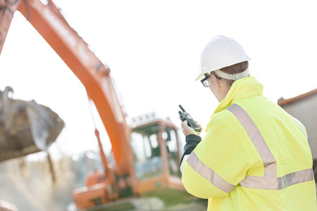 Supervisor using walkie-talkie at construction site against clear sky Stock Photo