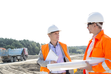 building contractor: Engineers discussing at construction site against clear sky LANG_EVOIMAGES