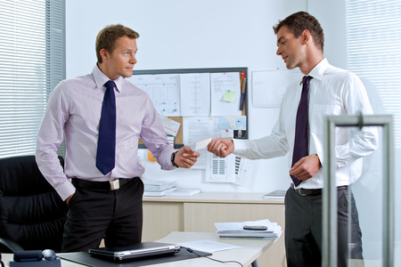 visiting card: Businessman giving visiting card to colleague LANG_EVOIMAGES