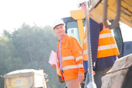 supervisores: Los supervisores que discuten en el sitio de construcci�n en d�a soleado