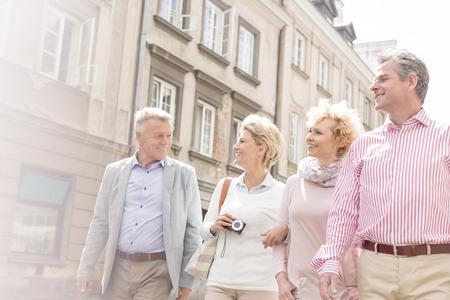 personas caminando: Amigos felices hablando mientras camina en la ciudad