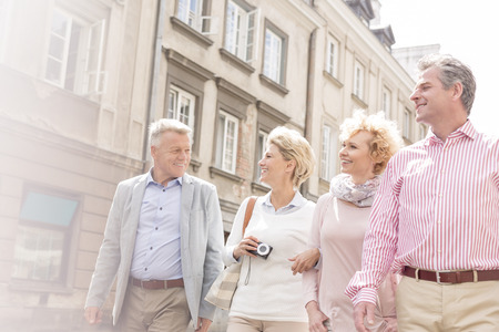 4 people: Happy friends talking while walking in city