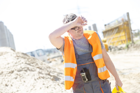 Tired construction worker wiping forehead at site Stock Photo