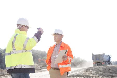 supervisores: Supervisores en discusiones en el sitio de construcci�n contra el cielo claro LANG_EVOIMAGES