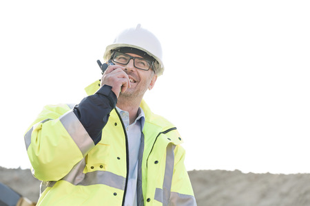 ���clear sky���: Happy supervisor using walkie-talkie at construction site against clear sky