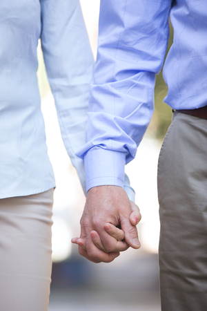 50s adult: Midsection of middle-aged couple holding hands outdoors