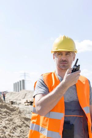 supervisor: Confident supervisor using walkie-talkie at construction site against sky