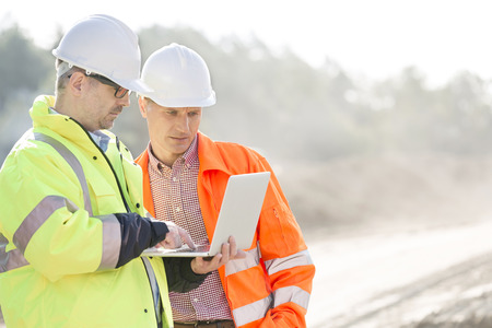 work safety: Supervisors using laptop at construction site
