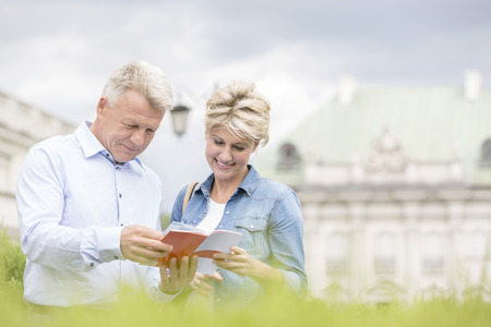 50s adult: Smiling middle-aged couple reading guidebook outdoors