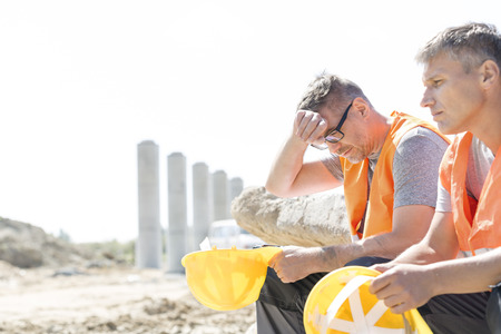 tired person: Tired supervisor sitting with colleague at construction site